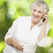 Portrait of senior woman talking on mobile against a nature back — Stock Photo #11581010