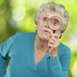 Portrait of senior woman looking through a magnifying glass agai — Stock Photo #11581019