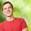 Portrait of young man smiling against a nature background — Stock Photo #11581055