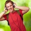 Portrait of cheerful young student listening music with headphon — Stock Photo #11581094