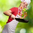 Portrait of young cook man cooking vegetables against a nature b — Stock Photo #11581138