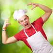 Portrait of young cook man wearing apron doing aggressive gestur — Stock Photo