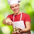 Stock Photo: Portrait of young cook man pressing a golden bell against a natu
