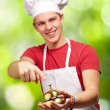 Portrait of young cook man pressing a golden bell against a natu — Stock Photo