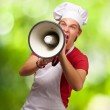 Portrait of young cook man screaming with megaphone against a na — Stock Photo