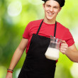 Portrait of young cook man holding milk jar against a nature bac — Stock Photo