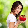 Portrait of young woman holding a cereal bowl against a nature b — Stock Photo