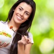 Portrait of healthy woman eating salad against a nature backgrou - Stockfoto