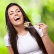 Stock Photo: Portrait of young woman holding sushi against a nature backgroun