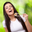 Portrait of young woman holding sushi against a nature backgroun — Stock Photo