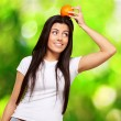 Portrait of young woman holding orange on her head over nature b — Стоковое фото