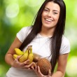 Portrait of young woman holding tropical fruits against a nature — Stock Photo #11581587