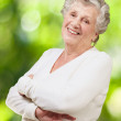 Portrait of senior woman smiling against a nature background — Stock Photo