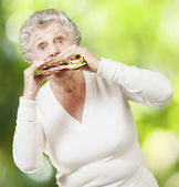 Senior woman eating a healthy sandwich against a nature backgrou — Stock Photo