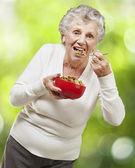 Senior mujer comiendo cereales de un tazón de fuente roja contra un naturaleza b — Foto de Stock