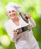Portrait of cook senior woman opening sauce pan against a nature — Stock Photo
