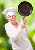 Cook senior woman angry trying to hit with pan against a nature — Stock Photo