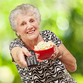 Portrait of senior woman holding pop corn bowl and changing chan — Stock Photo