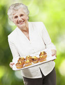 Senior woman smiling and holding a tray with muffins against a n — Stock Photo