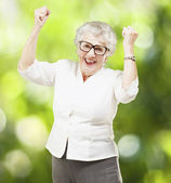 Portrait of a cheerful senior woman gesturing victory against a — Stockfoto