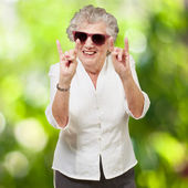 Portrait of a happy senior woman doing rock symbol against a nat — Stock Photo