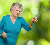 Senior woman holding a rotten banana against a nature background — Stock Photo