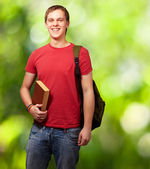 Portrait of young student holding book and carrying backpack aga — Foto de Stock