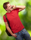 Portrait of young man talking on mobile against a nature backgro — Stock Photo