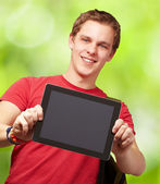 Portrait of young man holding a digital tablet against a nature — Stock Photo