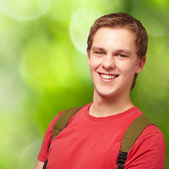 Portrait of young student man smiling and wearing backpack again — Stock Photo