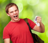 Young angry student man roughing a sheet against a nature backgr — Stock Photo
