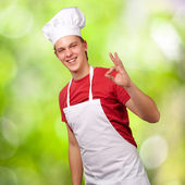 Portrait of young cook man doing success symbol against a nature — Stock Photo