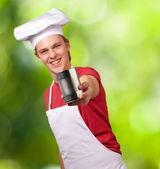 Portrait of young cook man holding a metal tin can against a nat — Stock Photo