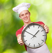 Portrait of young cook man holding clock against a nature backgr — Stock Photo