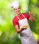 Retrato de hombre joven cocinero holding caja huevo contra una naturaleza — Foto de Stock