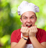 Portrait of young cook man screaming against a nature background — Stock Photo