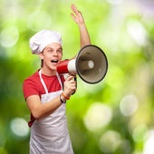 Portrait of young cook man shouting with megaphone against a nat — Stock Photo