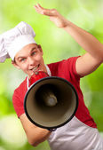 Portrait of happy cook man shouting using megaphone against a na — Stockfoto