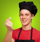 Portrait of young cook man holding euro coin and piggy bank over — Stock Photo