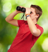 Portrait of young man looking through a binoculars against a nat — Stock Photo