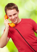 Portrait of young man talking on vintage telephone against a nat — Stock Photo