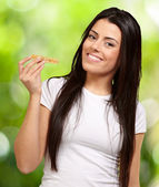 Portrait of young woman eating cereal bar against a nature backg — Fotografia Stock