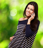 Young woman talking on mobile against a plants background — Stock Photo