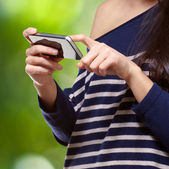 Portrait of young woman touching a modern mobile against a natur — Stock Photo