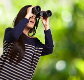 Portrait of young girl looking through a binoculars against a na — Stock Photo