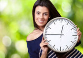 Portrait of young woman holding clock against a nature backgroun — Stock Photo