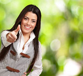 Portrait of a pretty young girl doing good gesture against a nat — Stock Photo