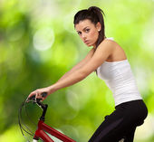 Portrait of young woman cycling against a nature background — Stock Photo