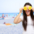 Woman On A Beach Covering Eyes With Lemon — Stock Photo #11658865