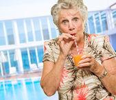 Portrait Of A Elderly Woman Drinking Juice — Stock Photo